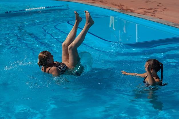 Babcia i wnuczka w basenie babcia wywraca się do góry nogami z dmuchanego koła do...