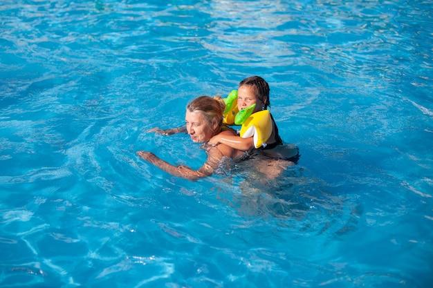 Babcia i wnuczka w basenie dziewczyna w dmuchanych rękawach jeździ na grzbiecie młodego ...