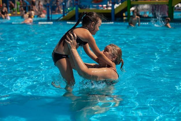 Babcia i wnuczka w basenie młoda babcia rzuca dziewczynę w nadmuchiwany krąg ...