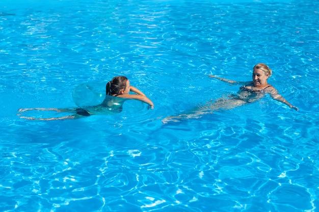 Babcia i wnuczka w basenie młoda emerytka i dziewczyna pływają w chłodnej wodzie...