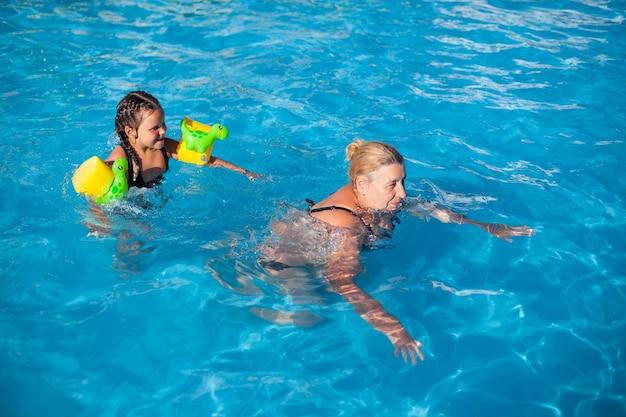 Babcia i wnuczka w basenie piękna babcia i pięcioletnia wnuczka w zielonym...