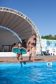 Babcia i wnuczka w basenie. wesoła babcia i urocza wnuczka radośnie wskakują do wody od strony basenu, chwila latania i podskakiwania w powietrzu.