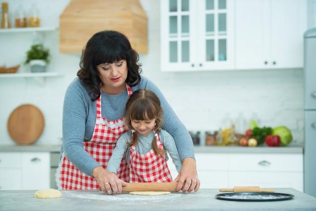 Babcia i wnuczka wspólnie gotują pizzę, wałkują ciasto wałkiem. rodzinne tradycje kulinarne.