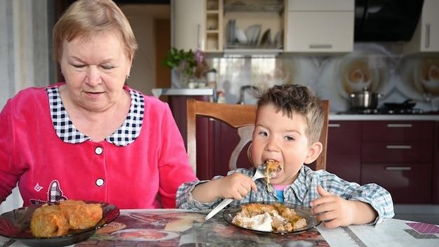 Babcia i wnuk jedzą przy stole.