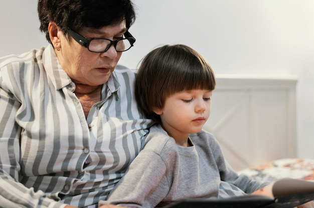 Babcia i wnuk razem czytają w domu