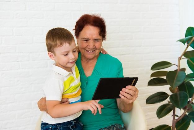 Babcia i wnuk używają w domu cyfrowego tabletu