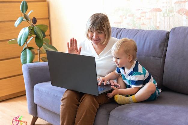 Babcia i wnuk za pomocą laptopa w domu. szczęśliwa dojrzała starsza kobieta z wnukiem trzyma wideorozmowę z przyjaciółmi, z bliska. starsza kobieta bawi się, rozmawia z dorosłymi dziećmi przez internet