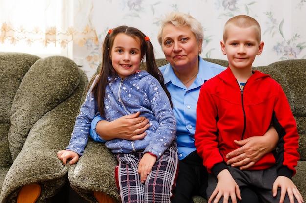 Babcia i wnuki siedzą razem na kanapie w salonie