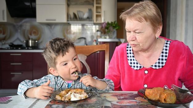 Babcia karmi wnuka w kuchni.