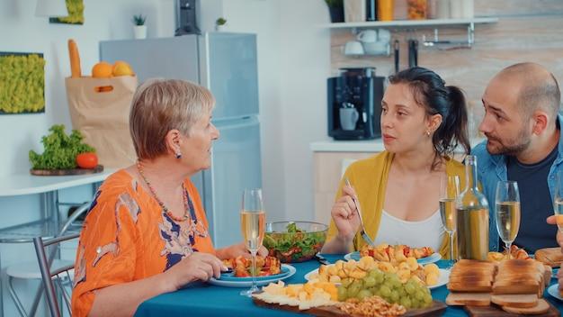 Babcia klika i dyskutuje podczas obiadu. wielopokoleniowe, cztery osoby, dwie pary chętnie rozmawiające i jedzące podczas wykwintnego posiłku, ciesząc się czasem w domu, w kuchni siedząc przy barze