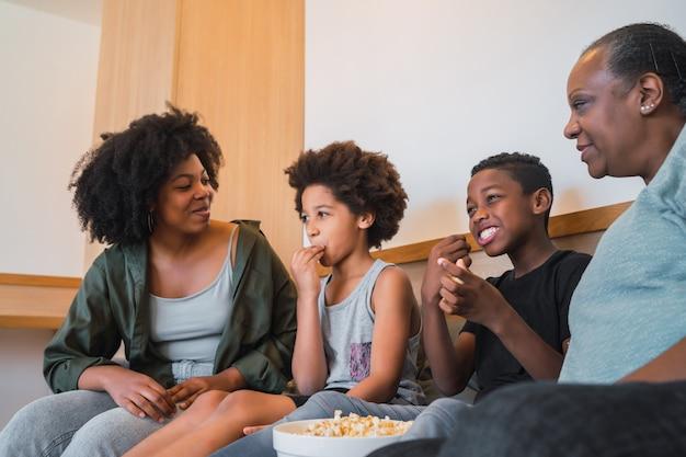 Babcia, matka i dzieci oglądają film w domu.