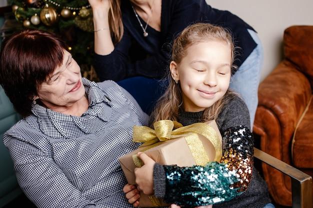 Babcia obejmująca i dając wnuczce prezent na boże narodzenie. szczęśliwa rodzina koncepcja.