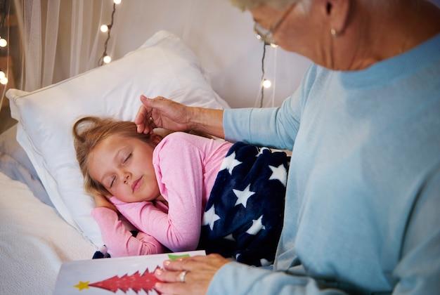 Babcia pieszcząca twarz wnuczki