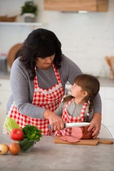 Babcia pomaga wnuczce kroić kiełbasę na plasterki w kuchni. gotowanie kanapek i pizzy. rodzina w kraciastych fartuchach.