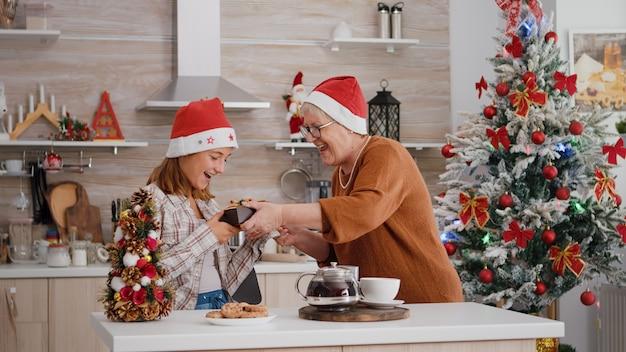 Babcia przynosi opakowanie prezentu ze wstążką wnuczce cieszącej się świętami