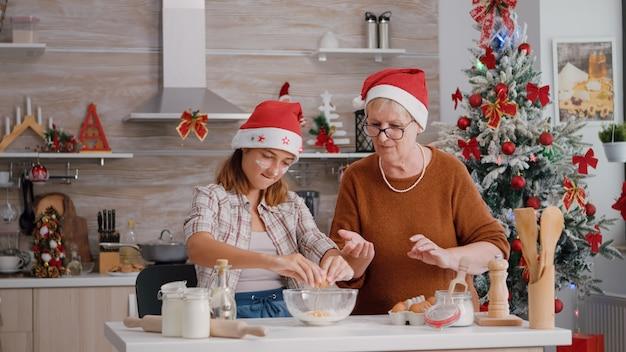 Babcia rozbija jajko pomagając wnukowi przygotować świąteczne ciasto w kuchni kulinarnej