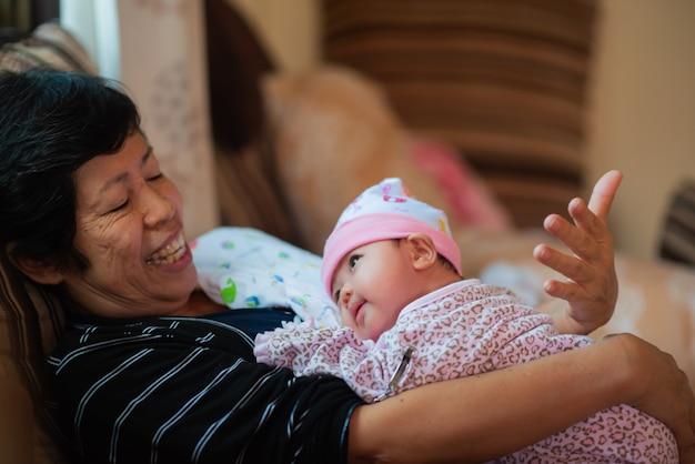 Babcia ściska jej wnuczki i ono uśmiecha się, miłości pojęcie