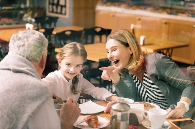 Babcia się śmieje. piękna blond włosa babcia śmiejąca się, słuchająca swojej inteligentnej wnuczki