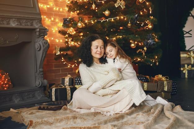 Babcia siedzi z wnuczką. świętowanie bożego narodzenia w przytulnym domu. kobieta w białym swetrze z dzianiny.