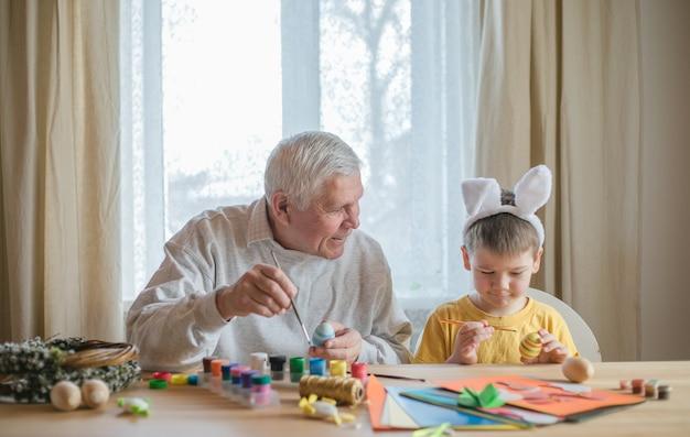 Babcia szczęśliwy starszy mężczyzna przygotowuje się do wielkanocy z wnukiem. portret uśmiechniętego chłopca z uszami królika, malowane kolorowe jajka na wielkanoc