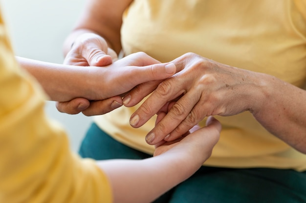 Babcia trzyma dziecko za ręce z bliska
