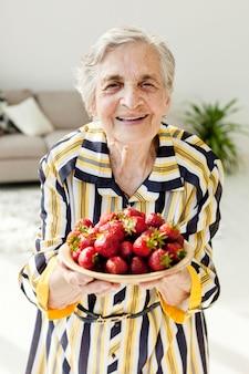Babcia trzyma świeże truskawki