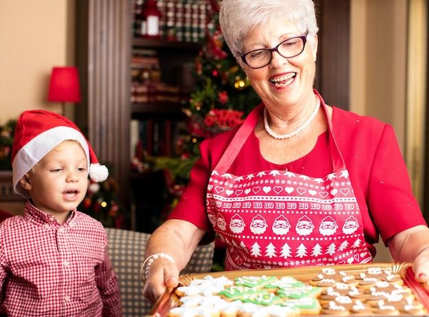 Babcia trzyma tacę z ciasteczka świąteczne