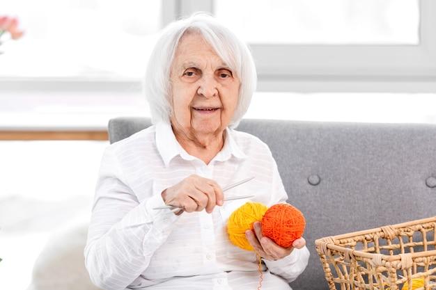 Babcia uczy robić na drutach wnuczkę