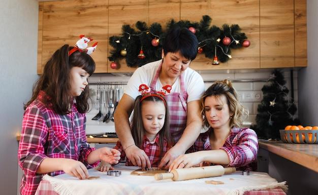 Babcia uczy swoje dzieci i wnuki gotować ciasteczka według starej receptury.