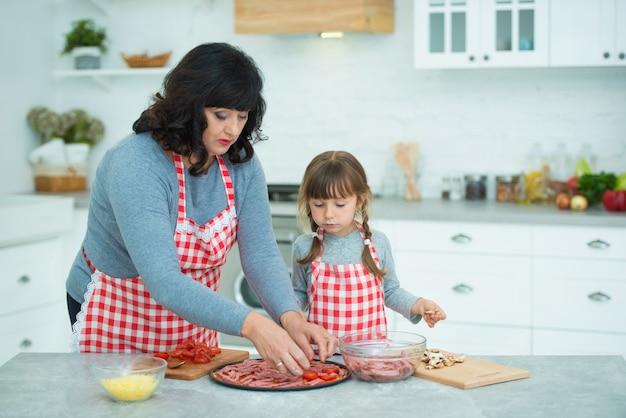 Babcia uczy wnuczkę gotowania pizzy. na cieście ułożyć kiełbasę i nadzienie. gotowanie w kuchni.