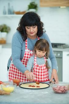 Babcia uczy wnuczkę gotowania pizzy. rozłóż keczup na cieście. gotowanie w kuchni.