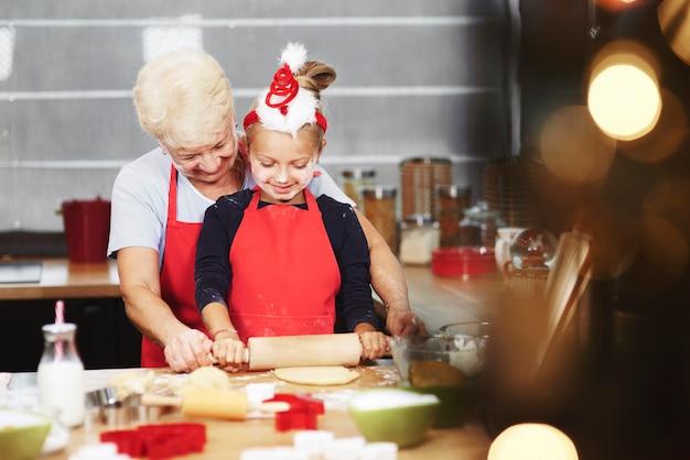 Babcia uczy wnuczkę rozwałkować ciasto