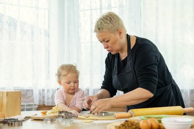 Babcia w czarnym fartuchu uczy swoją uroczą małą wnuczkę robić ciasteczka