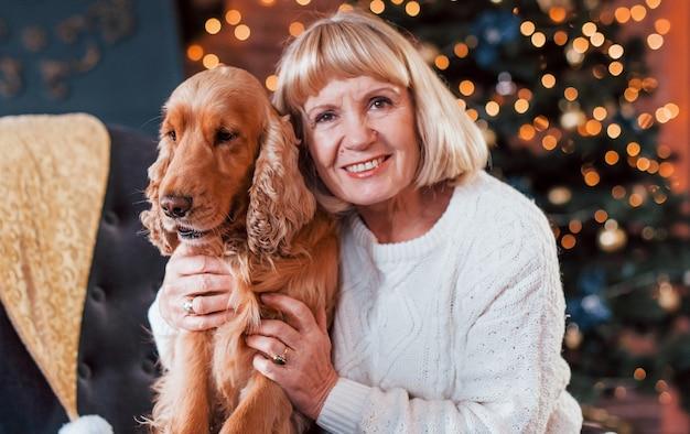 Babcia w domu z psem w świątecznym pokoju.
