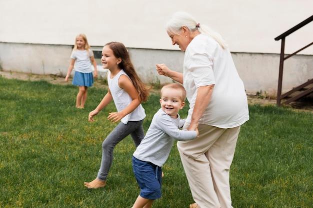 Babcia w pełnym ujęciu bawi się z dziećmi