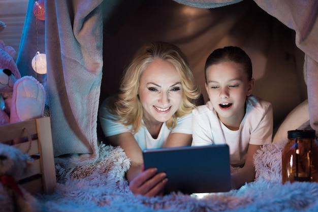 Babcia z dziewczyną oglądają wideo w kocowym domu w nocy