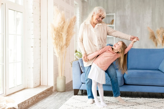 Babcia z dziewczyną tańczy w domu