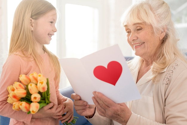 Babcia z kwiatami i kartkę z życzeniami od dziewczyny
