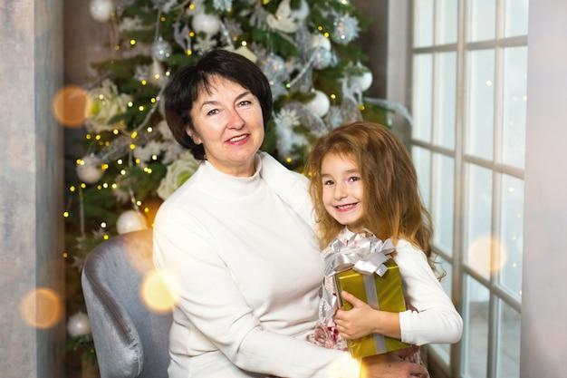 Babcia z małą dziewczynką na tle ozdób choinkowych i duże okno. rodzinne wakacje, emocje, pudełko. wnuczka na kolanach babci. nowy rok
