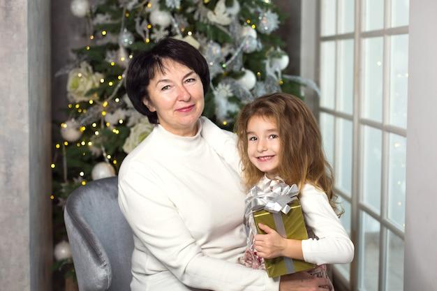 Babcia z małą dziewczynką na tle ozdób choinkowych i dużym oknem.