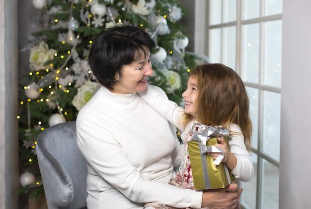 Babcia z małą dziewczynką z dekoracjami świątecznymi i dużym oknem. urlop rodzinny, emocje, pudełko. wnuczka na kolanach babci. nowy rok