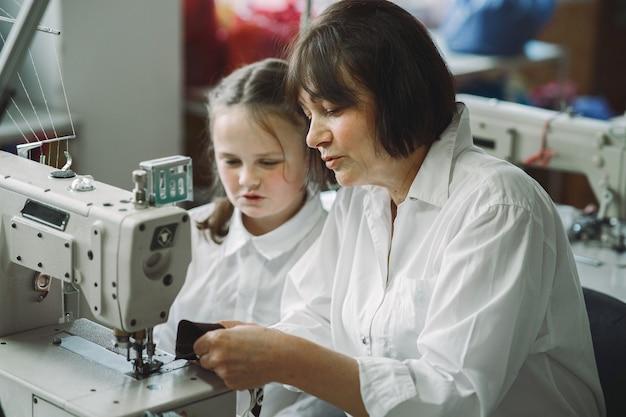 Babcia z małą wnuczką szyje ubrania w fabryce