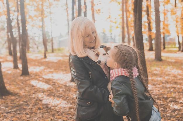 Babcia z wnuczką w jesiennym parku dziewczyna przytula babcię i jej jack russell terrier