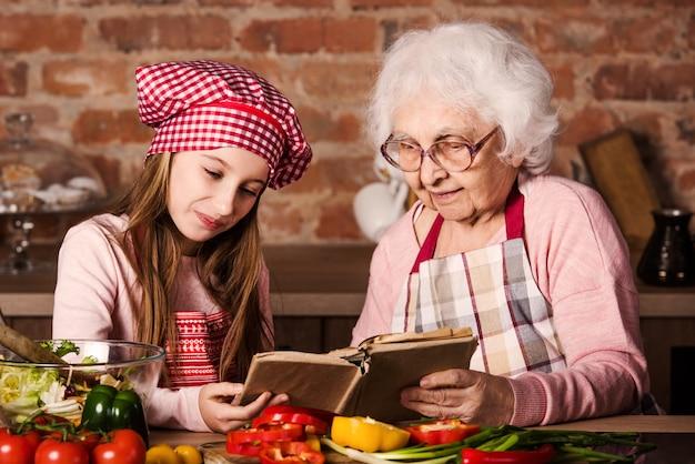 Babcia z wnuczką za pomocą książki kucharskiej