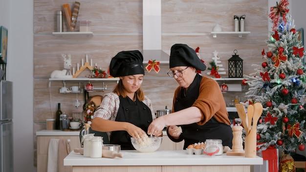 Babcia z wnukiem przygotowuje zimowy domowy deser ciasteczkowy