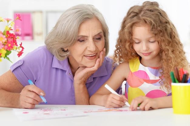 Babcia ze swoją uroczą wnuczką rysującą na tle