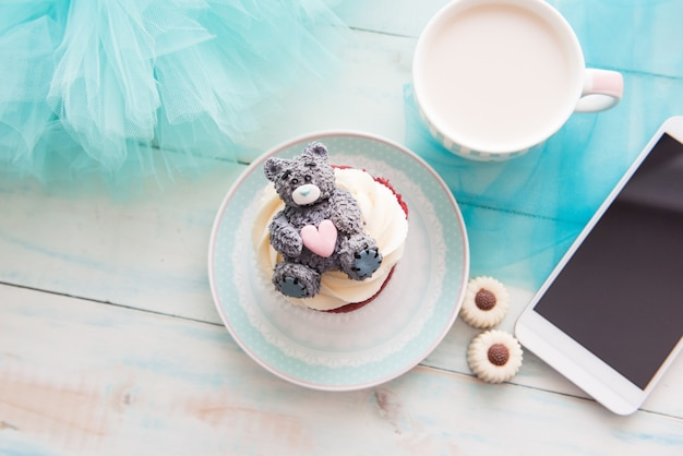 Babeczka, kubek, telefon, cukrowy miś, czekoladki i smartfon na turkusowym tle