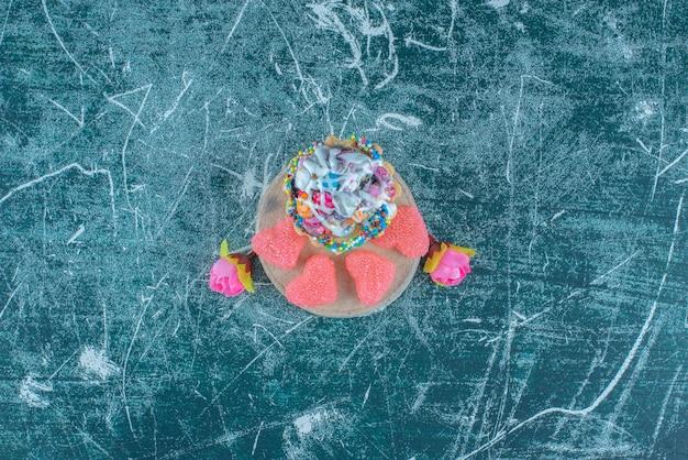 Babeczka, marmolady i kwiatowe corollas spakowane razem na niebieskim tle. wysokiej jakości zdjęcie