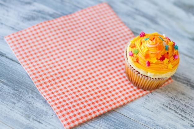 Babeczka na czerwonym cieście serwetkowym w kratkę z pomarańczowym lukrem spróbuj nowego deseru w restauracji małe cukrowe kwiatki