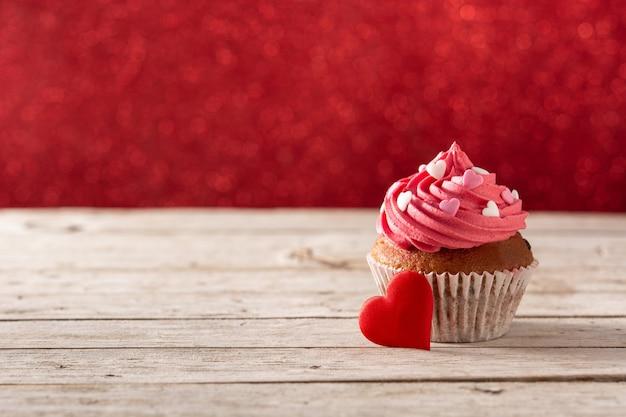 Babeczka ozdobiona serduszkami z cukru na walentynki na drewnianym stole i czerwonym tle